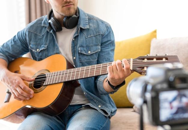 Blogger gravando a si mesmo enquanto tocava guitarra Foto gratuita