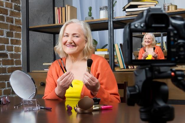 Blogger idoso da mulher que a grava fazendo compo o vídeo em linha pela câmera, Foto Premium