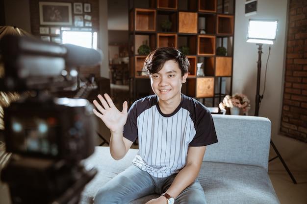 Blogger jovem asiático fazer revisão usando a câmera em primeiro plano Foto Premium