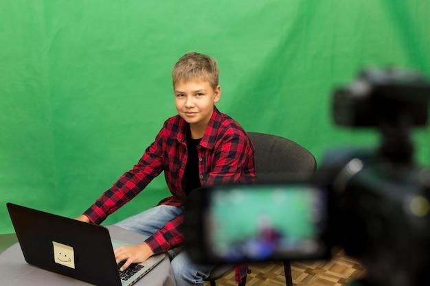 Blogger jovem rapaz grava vídeo em um verde Foto Premium
