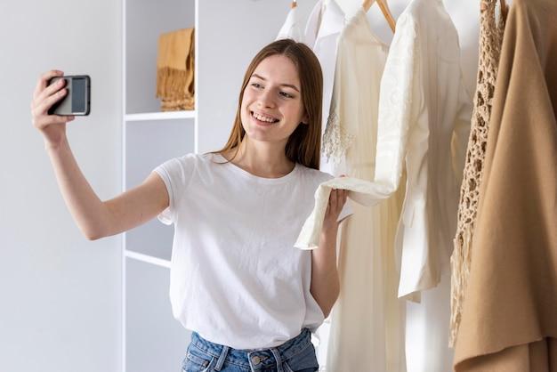 Blogger mostrando suas roupas e usando smartphone Foto gratuita