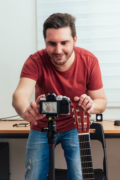 Blogger preparando a câmera para gravar a aula de violão em seu estúdio em casa Foto Premium