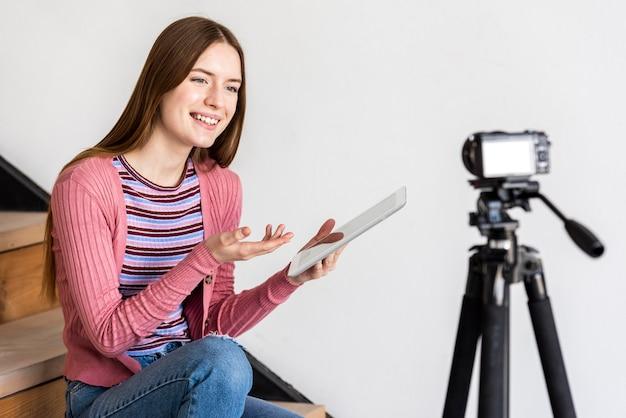 Blogger usando tablet e conversando com a câmera Foto gratuita