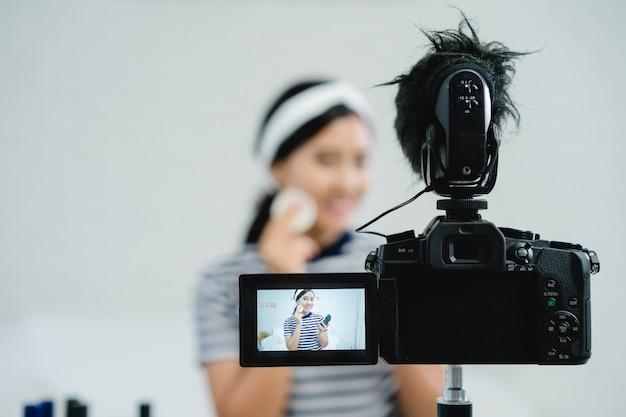 Blogueiro de beleza apresenta cosméticos de beleza enquanto está sentado na câmera frontal para gravação de vídeo Foto gratuita