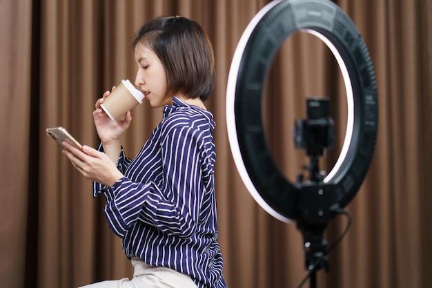 Blogueiro de mulher tomando café do copo de papel para viagem durante o uso do telefone móvel com luz do anel. Foto Premium
