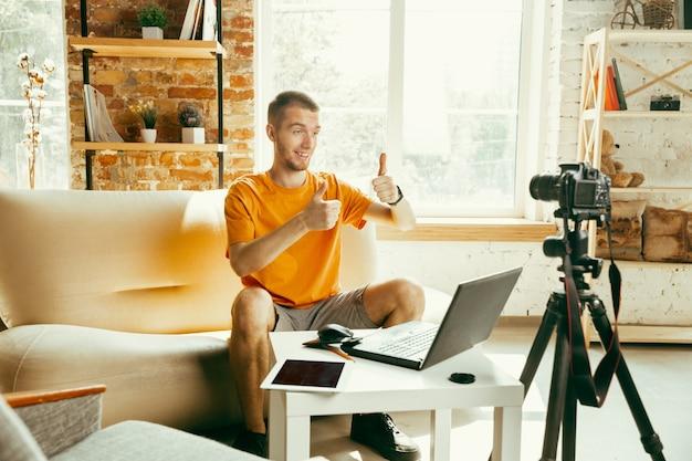Blogueiro do sexo masculino, caucasiano, com câmera gravando análise de vídeo de gadgets em casa Foto gratuita