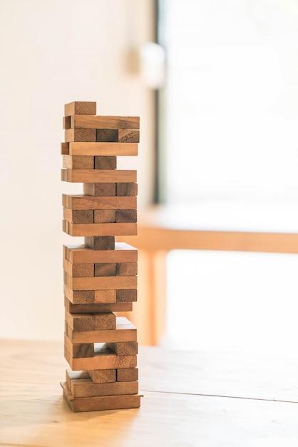 Bloqueia o jogo de madeira (jenga) na mesa de madeira Foto gratuita