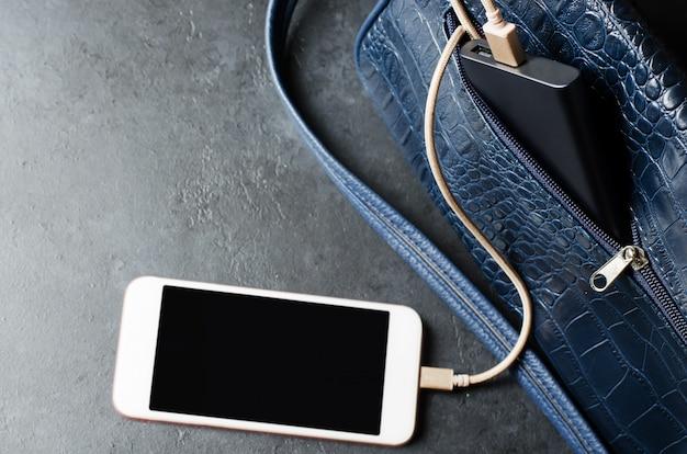 Blue power bank e telefone na bolsa feminina. fundo de concreto cinza escuro. copie o espaço Foto Premium