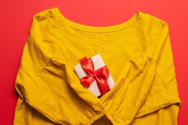 Blusa amarela do algodão das mulheres ee caixa de presente no fundo vermelho. Foto Premium