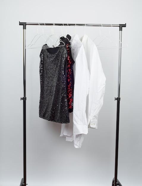 Blusa feminina preta com lantejoulas vermelhas, camisas brancas masculinas penduradas em um cabide de ferro branco Foto Premium