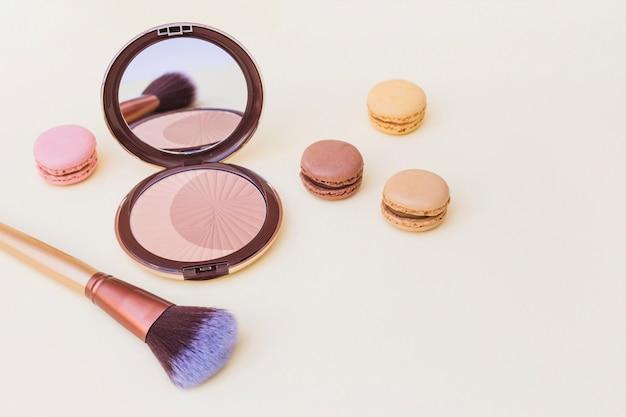 Blush com pincel macaroon e maquiagem no fundo bege Foto gratuita