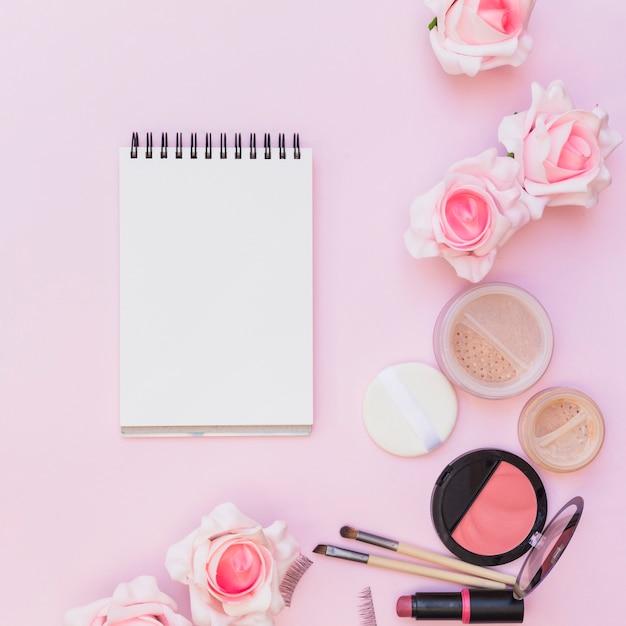 Blusher; batom; esponja; pincel de maquiagem com rosas em fundo rosa Foto gratuita