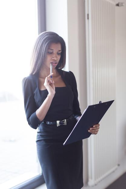 Boa aparência jovem mulher de negócios em preto forte suite espera tablet Foto Premium