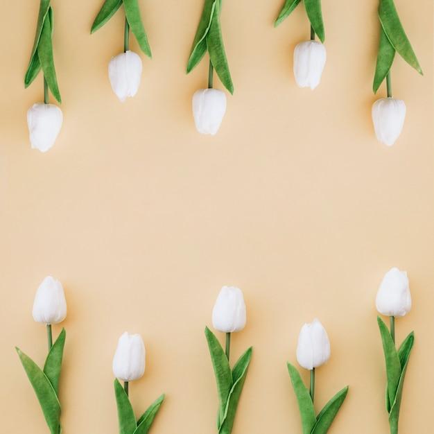 Boa composição com tulipas em fundo amarelo com espaço no meio Foto gratuita
