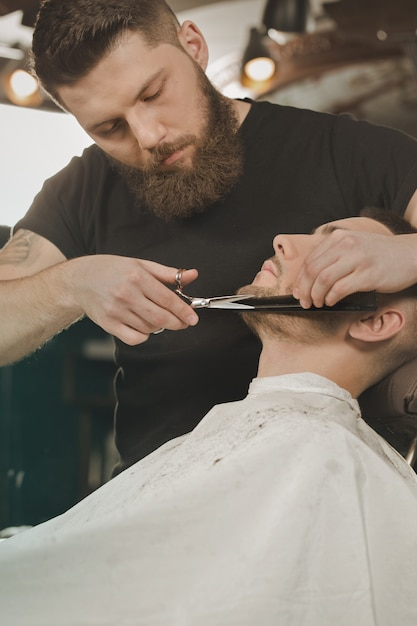 Boa tesoura velha. vertical, tiro, barbeiro, aparando, barba, seu, cliente, usando, tesouras Foto Premium