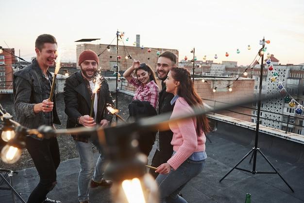 Boas festas. brincando com estrelinhas no telhado. grupo de jovens amigos lindos Foto gratuita