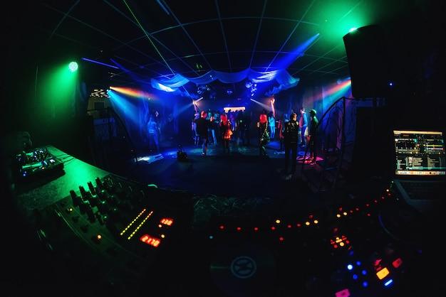 Boate com gente dançando na pista de dança, foliões em uma festa e música do dj Foto Premium
