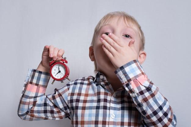 Bocejar menino loiro com um despertador vermelho nas mãos. conceito de manhã Foto Premium