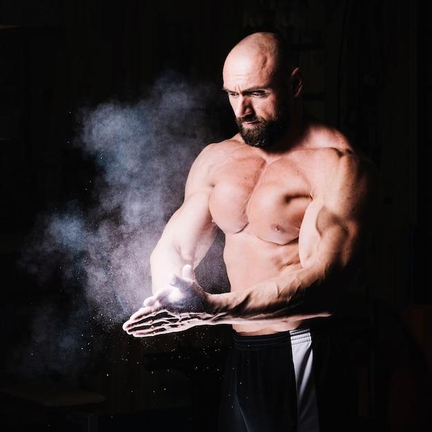 Bodybuilder aplaudindo as mãos com talco Foto gratuita