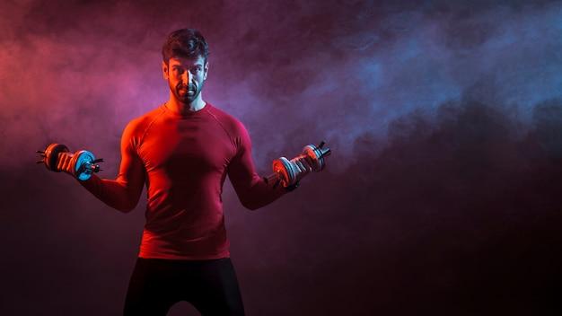 Bodybuilder com pesos no estúdio Foto gratuita