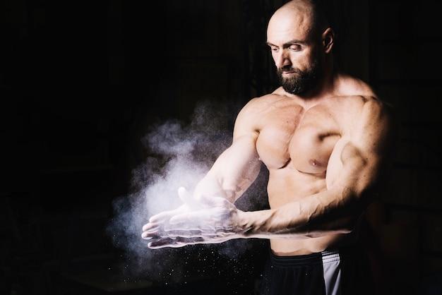 Bodybuilder esfregando as mãos com talco em pó Foto gratuita