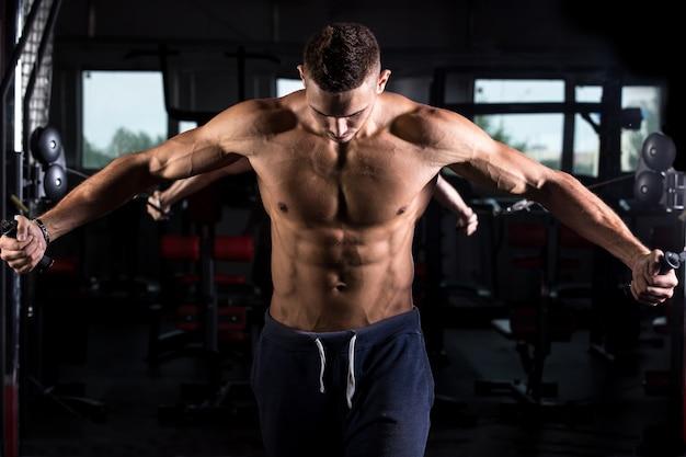 Bodybuilder jovem usando equipamento de ginástica Foto gratuita