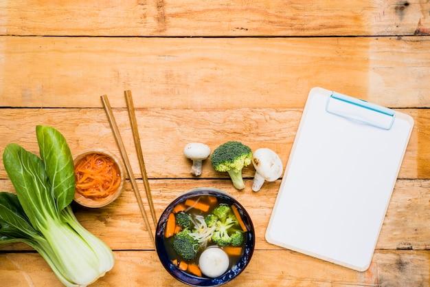 Bokchoy; cenoura; sopa de bola de peixe; pauzinhos e prancheta em branco sobre a mesa Foto gratuita