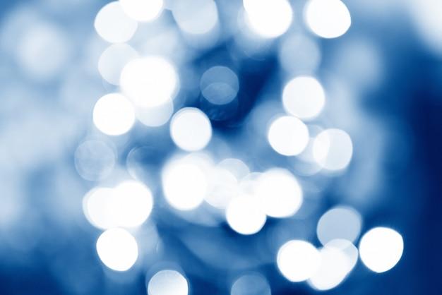 Bokeh azul turva e luzes decoradas árvore de natal em fundo preto para celebração do festival de férias Foto Premium
