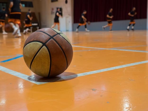 Bola de basquete na quadra com linha de lance livre, jogadores fora de foco Foto Premium
