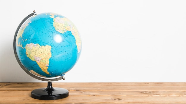 Bola de carrinho mapa global na mesa de madeira Foto Premium
