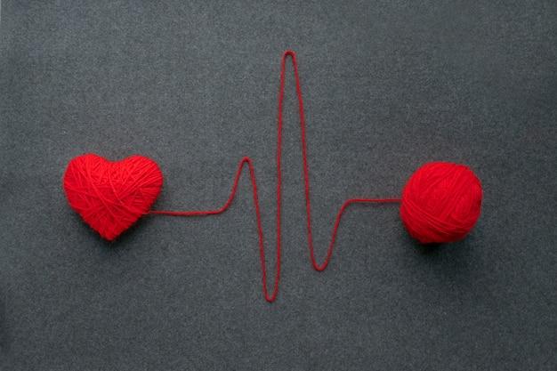 Bola de fio vermelho artesanal com coração coração e batimento cardíaco Foto Premium