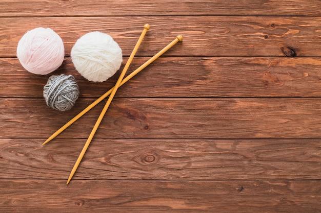 Bola de fios e crochê na prancha de madeira Foto gratuita