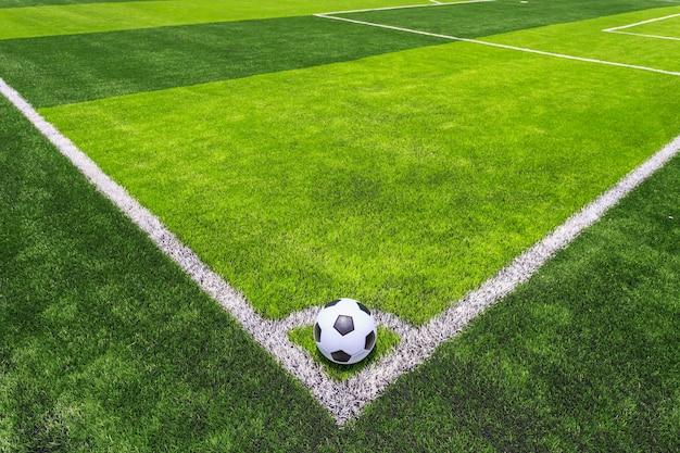 Bola de futebol clássico na relva verde escura e brilhante artificial Foto Premium