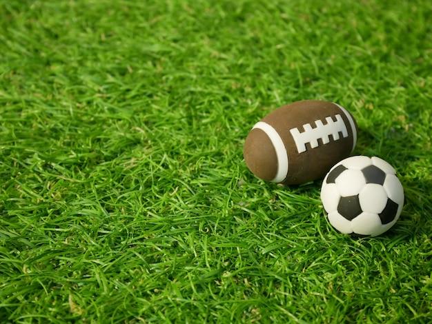 Bola de futebol e bola de rugby no campo de grama verde Foto Premium