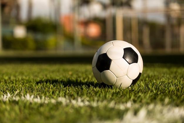 Bola de futebol em um campo gramado, sob o pôr do sol Foto Premium