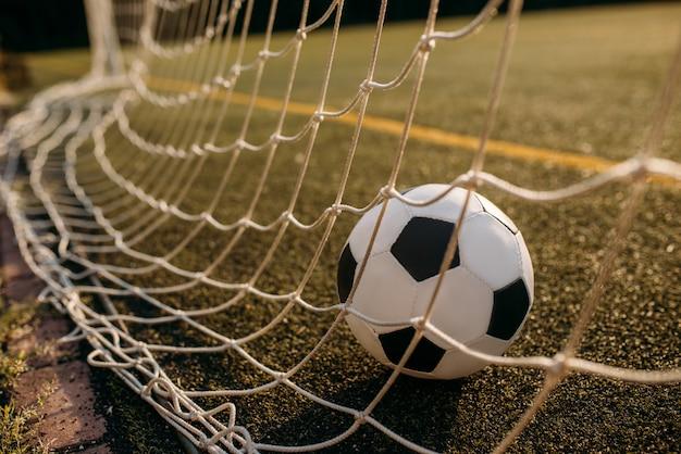 Bola de futebol na rede do portão. futebol em estádio ao ar livre, jogo de esporte ou conceito de gol Foto Premium