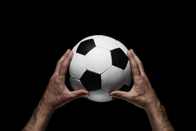 Bola de futebol nas mãos masculinas em um preto Foto Premium
