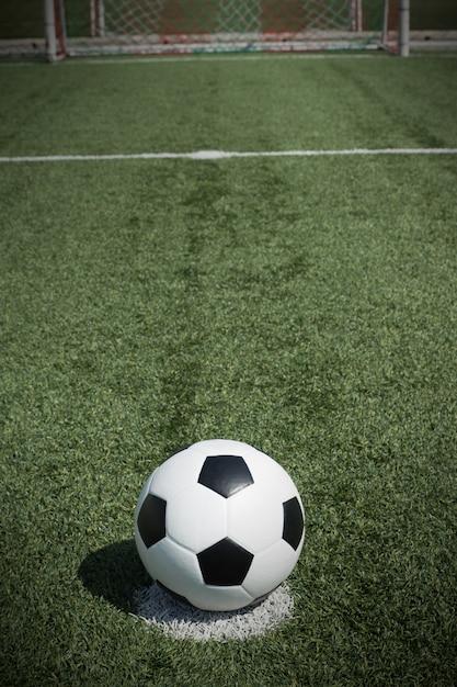 Bola de futebol no campo com goalnet na frente Foto Premium