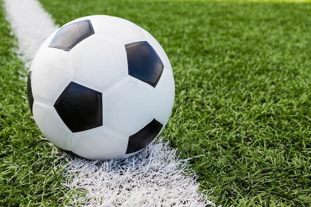 Bola de futebol no campo no fundo da linha branca Foto Premium