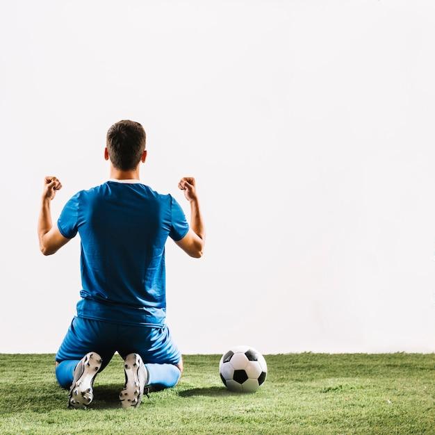 Bola de futebol perto de esportista sem rosto após a vitória Foto gratuita