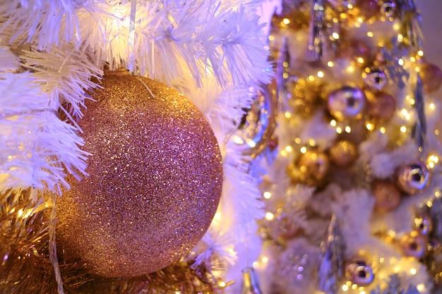 Bola de glitter rosa-ouro em forma de enfeite de natal com árvore de natal cintilante turva no fundo Foto Premium