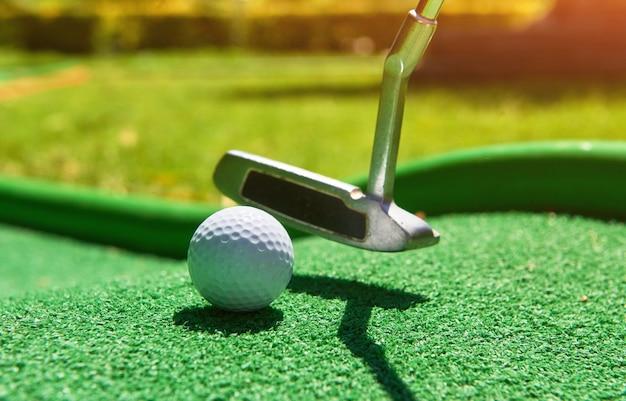 Bola de golfe e clube de golfe em grama artificial. Foto gratuita