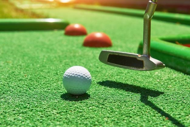Bola de golfe e clube de golfe em grama artificial. Foto Premium