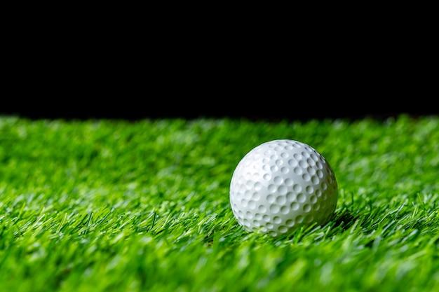 Bola de golfe na grama em preto Foto Premium