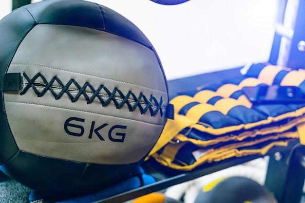 Bola de mecidina cinza com 6 kg de peso e outros equipamentos esportivos na academia. Foto Premium