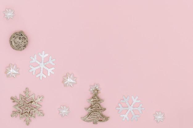 Bola de natal dourada, floco de neve, árvore de natal, arcos de presente em fundo rosa pastel Foto Premium