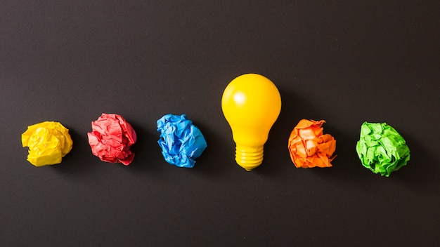 Bola de papel amassado colorido com lâmpada amarela contra fundo preto Foto gratuita