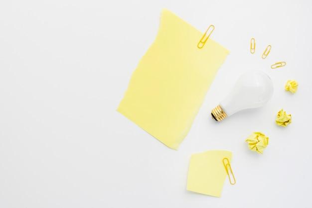 Bola de papel amassado com lâmpada branca e clipe de papel no fundo branco Foto gratuita