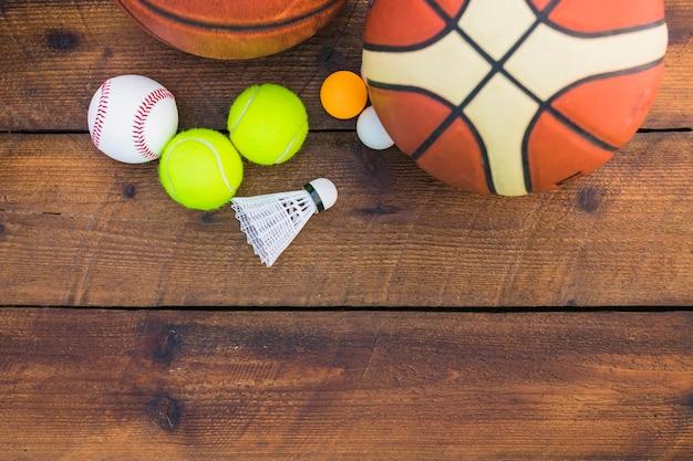 Bola de pingue-pongue; beisebol; peteca; bola de basquete e tênis na prancha de madeira Foto gratuita