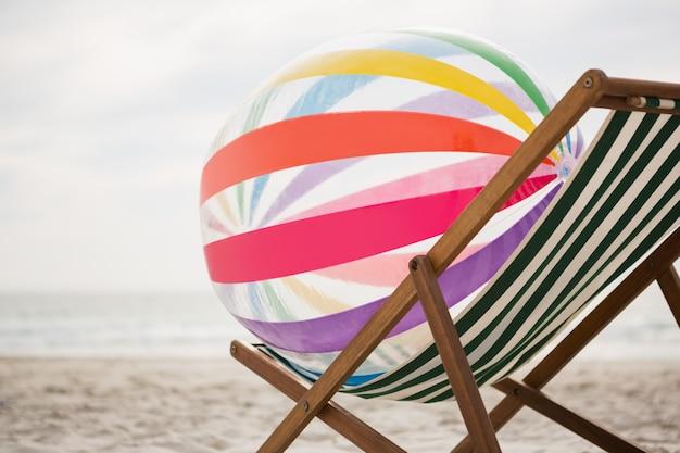 Bola de praia listrado mantidos em cadeira de praia vazia Foto gratuita